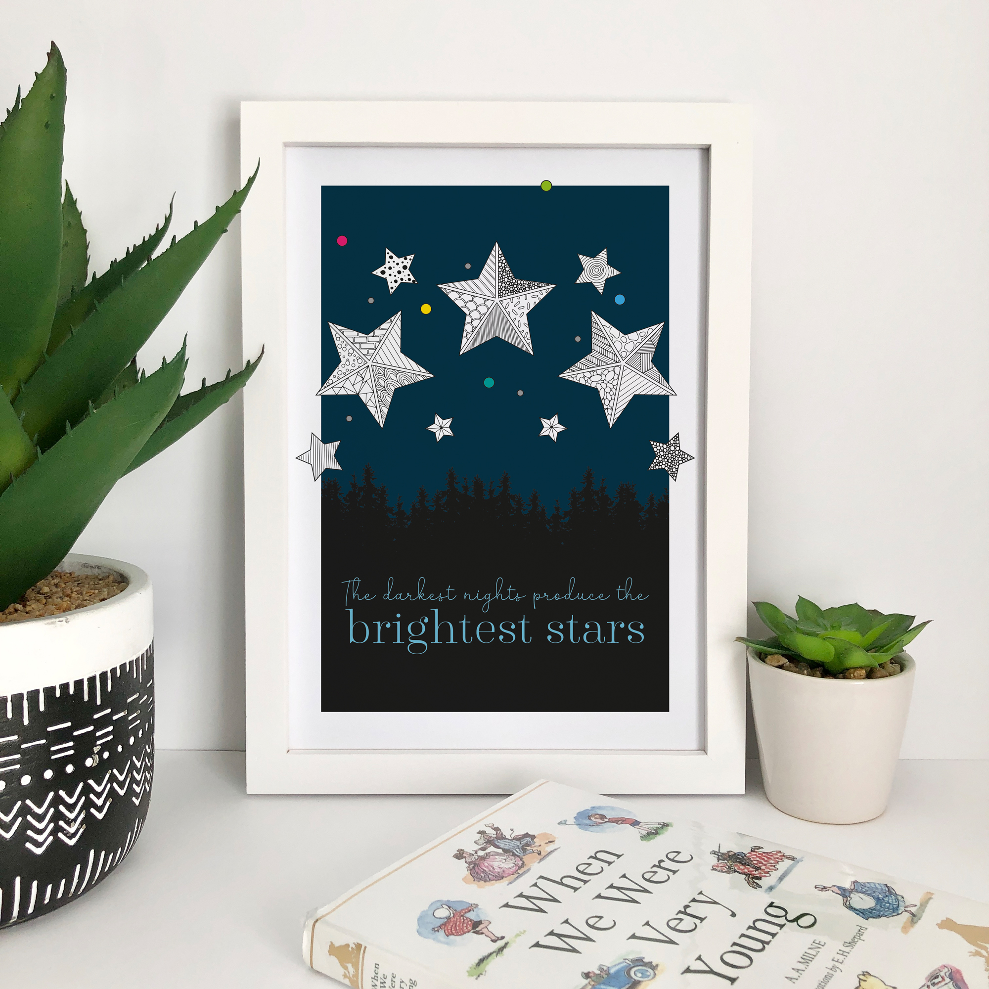 This design is available with a navy blue, grey, or rainbow background and features the phrase 'The darkest nights produce the brightest stars'.