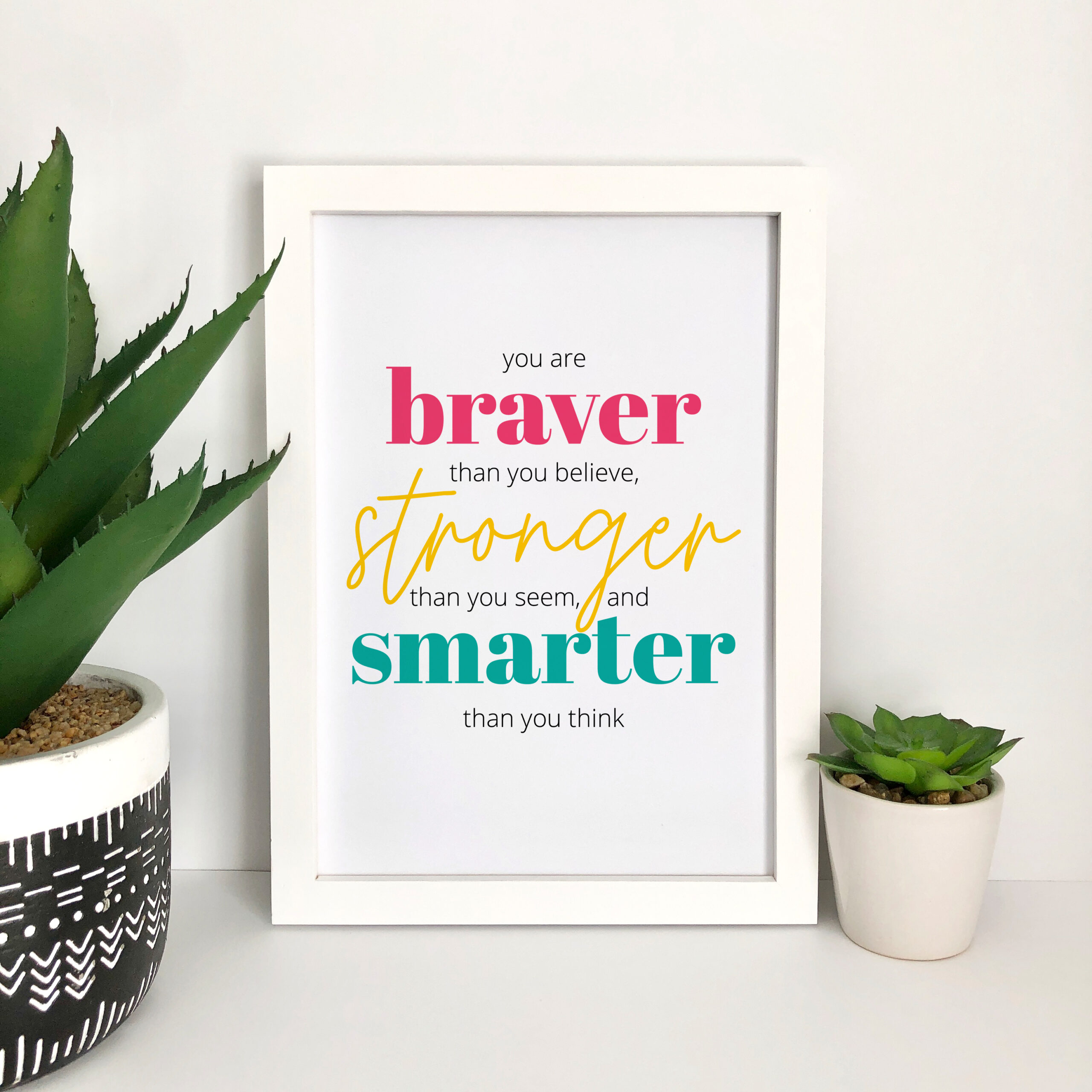 Art print in a white frame along with potted indoor plants. The design is a typography quote about Being Braver, Stronger, and Smarter