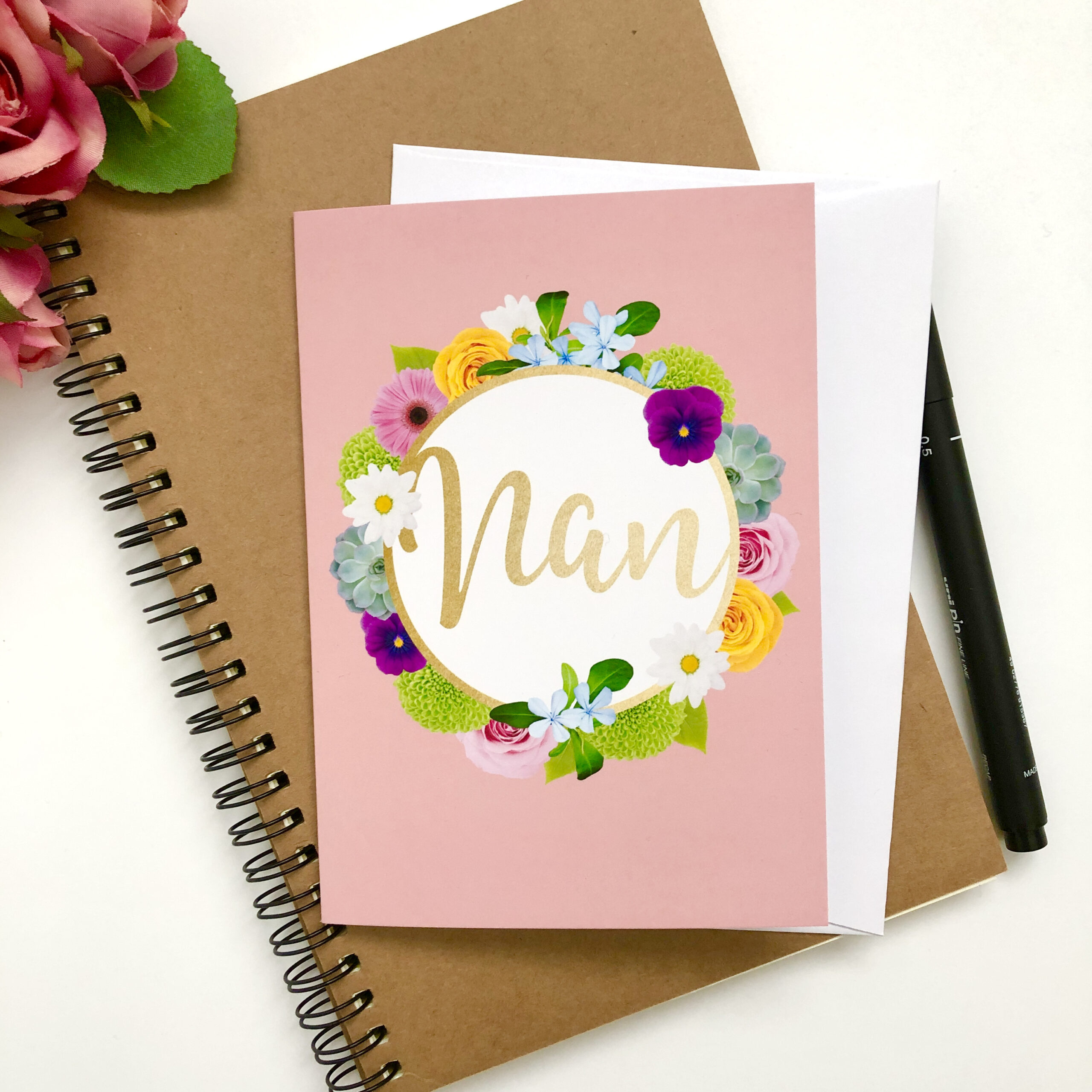 Greetings card for Nan featuring multicoloured floral wreath on a blush pink background