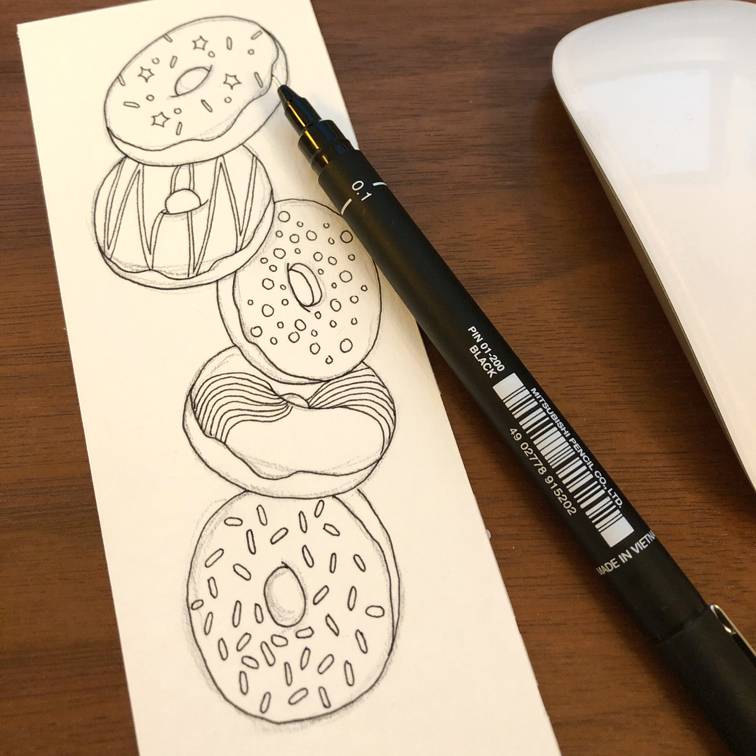 Line drawing of five falling doughnuts with sprinkles on a bookmark