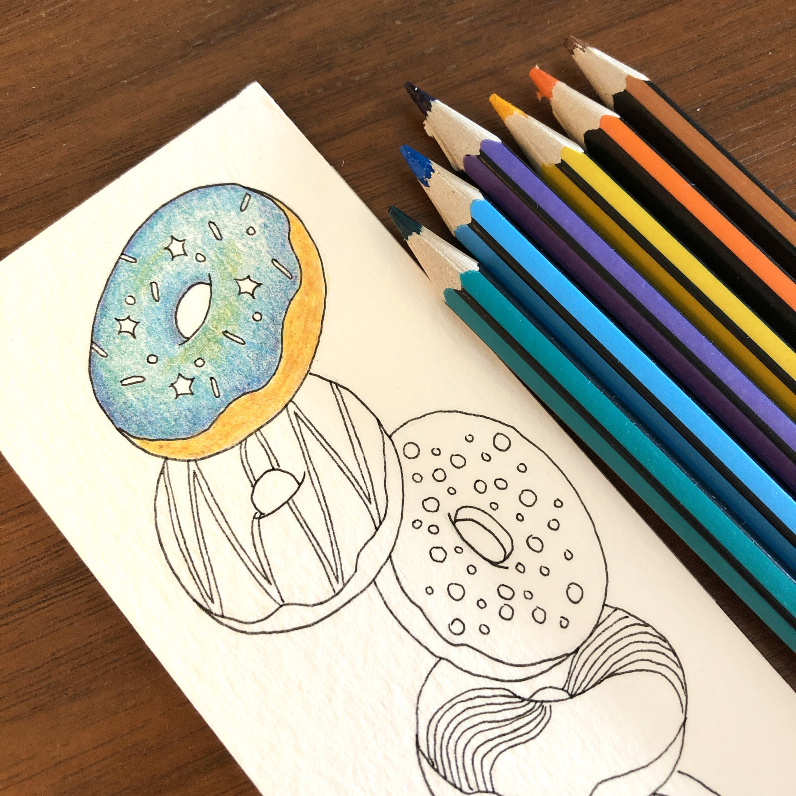 work in progress shot of a handcrafted bookmark featuring five falling doughnuts with coloured icing and sprinkles