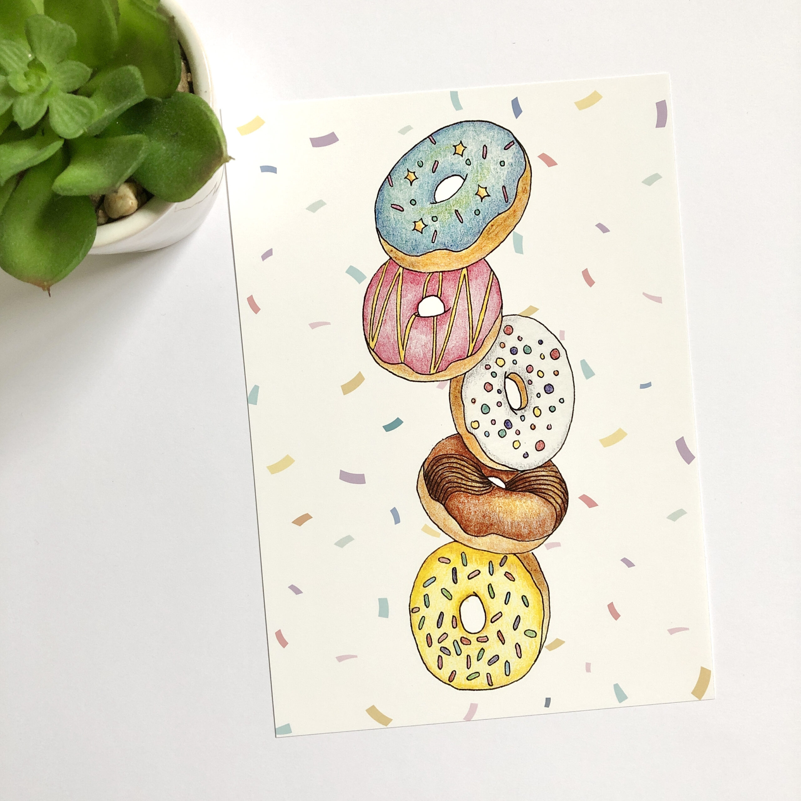 World Book Day art print featuring five falling doughnuts with coloured icing and sprinkles, with a multicoloured confetti background