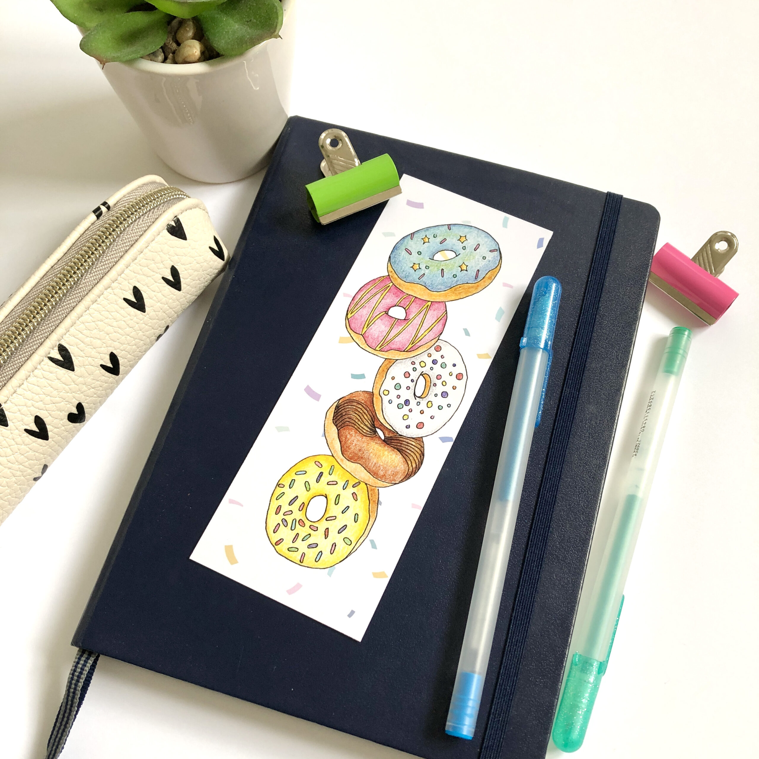 product shot of a printed bookmark featuring five falling doughnuts on top of a navy blue bullet journal